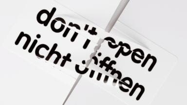 """Sicherheitsetiketten - Gerissenes Etikett mit der Aufschrift """"Nicht öffnen"""" auf weißer Oberfläche"""