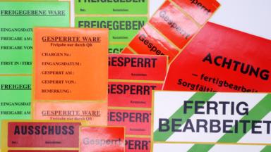 QS-Etiketten, darunter Freigabe- und Gesperrt-Etiketten, liegen in einem Stapel