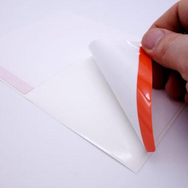 Wiederablösbare Etiketten - Ein quadratisches Etikett wird an der roten Abziehhilfe abgezogen