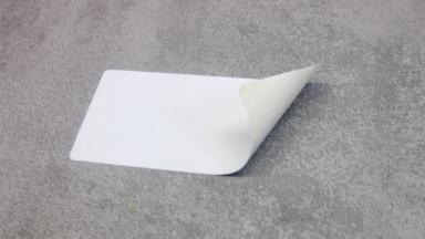 Etiketten für Möbelindustrien - Ein leicht angeknicktes und wiederablösbares Möbeletikett auf einer weichen Oberfläche